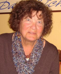Ingrid Decker blickt in die Kamera. Sie trägt einen braunen Pullover und einen passenden, blau gemusterten Schal.