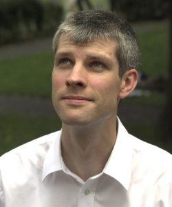 Foto Michael Teipel; er trägt ein weißes Hemd und blickt nach oben