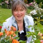 Die Fotografin Nathalie Dautel inmitten blühender Rosen. Direkt vor ihr ein Rosenstrauch in Orangetönen.