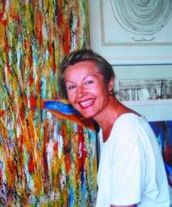 Foto der lachenden Autorin vor einem bunten, großflächigen Gemälde.