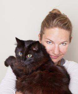 Verena Zimmer hat eine große braunschwarze Katze auf dem Arm.