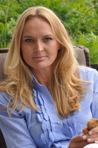 Eine Frau mit langen blonden Haaren und blauen Augen sitzt auf einem Gartenstuhl und blickt in die Kamera. Sie hält einen kleinen Teddy in ihren Händen.
