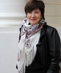 Foto Elena Ronina. Sie hat einen Fransenschal um den Hals drapiert und steht vor einer großen Säule.