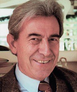 Auf diesem Foto trägt der Autor ein braunes Jakett mit passender Krawatte zu einem hellblauen Hemd. Er blickt lächelnd in die Kamera.