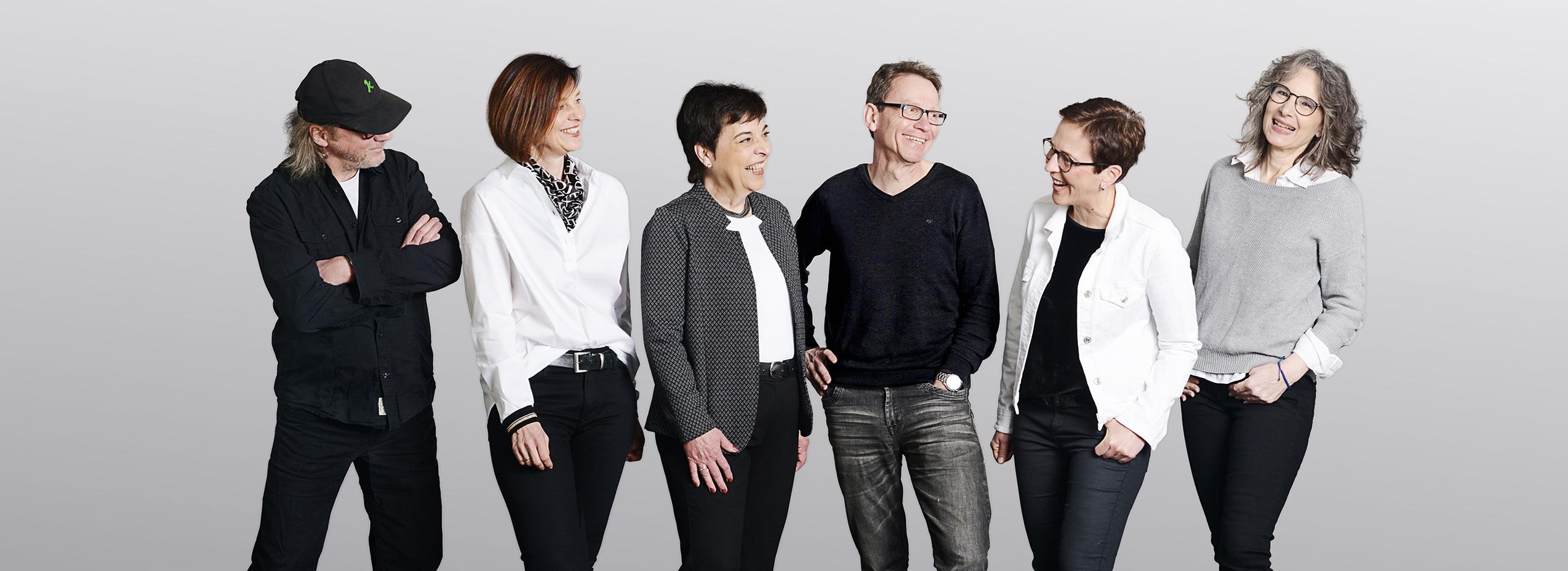 Foto des lachenden Teams. 5 Personen in lässiger Pose stehen in einer Reihe nebeneinander.